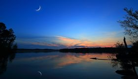 Crescent Moon over a Shining Lake Stock Photography