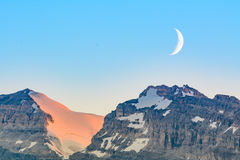 Crescent moon over snow capped mountains - Lake Louise - Canada. Crescent moon at sunset over the snow capped mountain ranges sourrounding Lake Louise - Canadian Royalty Free Stock Image