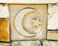 Crescent moon, symbol of Islam. Ceramic tile in old rock wall with crescent moon and star, the religious symbol of islam. Tile is one of a series of seven stock image