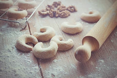 Crescent vanilla cookies, with some flour, walnuts and rolling pin. On a wooden table Royalty Free Stock Photography