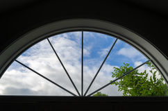 Crescent Window. Clouds float by this view through a crescent window Royalty Free Stock Photography