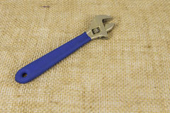 Crescent Wrench on Burlap. A crescent wrench with a blue handle sitting on a burlap background royalty free stock images