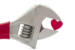 Crescent wrench and heart. On white stock image