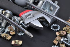 Crescent wrench screws and bolts. On black metal suraface stock image