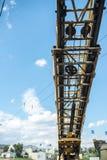 Crescimento amarelo do guindaste com ganchos em um fundo da nuvem da cidade Imagens de Stock Royalty Free