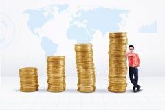 Crescimento das moedas do homem de negócios e de ouro no mapa do mundo Fotografia de Stock