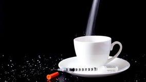 Crescimento de derramamento do açúcar granulado do branco no café do copo com a seringa no fundo preto filme