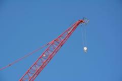 Crescimento vermelho do guindaste contra um céu azul Fotografia de Stock Royalty Free