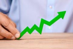 Crescita nelle vendite e nei profitti Freccia verde che indica su nelle mani dell'uomo immagine stock