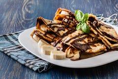 Crespones con crema del plátano y del chocolate Foto de archivo