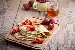 Crespones con las fresas frescas y la miel orgánica para el desayuno Imagenes de archivo