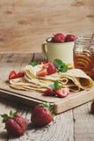 Crespones con las fresas frescas y la miel orgánica para el desayuno Imágenes de archivo libres de regalías