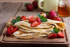 Crespones con las fresas frescas y la miel orgánica para el desayuno Fotografía de archivo libre de regalías