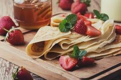 Crespones con las fresas frescas y la miel orgánica para el desayuno Imagen de archivo