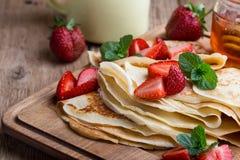 Crespones con las fresas frescas y la miel orgánica para el desayuno Fotos de archivo