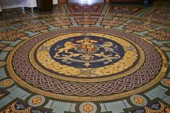 Circular royal coat of arms of UK on paved tiled floor inside historic Parliament House of Victoria State, Melbourne, Australia. Crest of United Kingdom monarch royalty free stock images