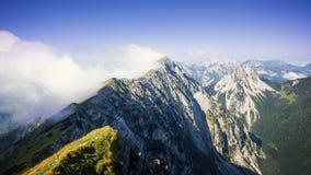 Cresta dell'alta montagna nascosta in nuvole durante l'alba, Koschuta, Slovenia Fotografie Stock