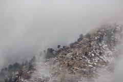 Cresta della montagna che compare attraverso la nebbia un giorno di inverno immagine stock libera da diritti