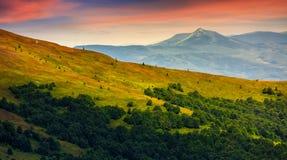 Cresta della montagna con il picco dietro il pendio di collina al tramonto Fotografia Stock