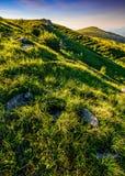 Cresta della montagna con il picco dietro il pendio di collina al tramonto Fotografia Stock Libera da Diritti