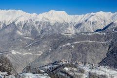 Cresta della montagna di Snowy e gruppo degli hotel nella stazione sciistica Soci di Rosa Khutor Immagine Stock