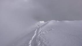 Cresta della sommità di una montagna nelle alpi svizzere con le piste e di una nebbia in maltempo Immagine Stock