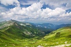Cresta e cielo blu della montagna con le nubi immagine stock