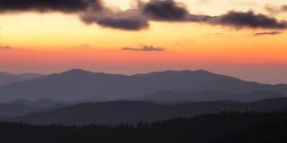 Cresta fumosa delle montagne al tramonto nuvoloso fotografie stock libere da diritti
