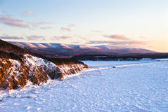 Crested in Color. Cape Breton Coastline in Winter Showing Low Angle Sun Rays hitting Pack Ice and Hill Tops Royalty Free Stock Images