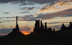 Cresting Sunrise Silhouette at Totem Pole in Monument Valley. Sunrise over Totem Pole butte in Monument Valley Tribal Park with sun kissed morning clouds Stock Photos