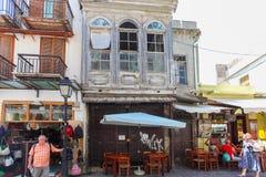 Creta de Rethymnon, ilha, Grécia, - 1º de julho de 2016: As construções velhas com cafés e as lojas pequenos são ficadas situadas Imagem de Stock