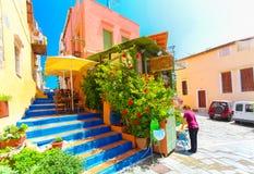 Creta de Rethymnon, ilha, Grécia, - 1º de julho de 2016: O café pequeno do cretan confortável com flores fora com e empregada de  Foto de Stock