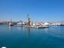 18 06 CRETA 2015, GRECIA, grúas del cargo y nave en el puerto marítimo Foto de archivo libre de regalías