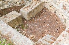 CRETA, GRECIA - noviembre de 2017: Marque con hoyos para los sacrificios, presentado con las piedras, el patio del oeste del pala fotos de archivo
