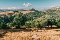 Creta Grecia, opinión sobre las montañas con las nubes bajas de la ejecución y los árboles azules del cielo y verdes Creta del su foto de archivo