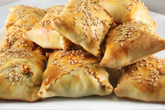 Cretan pies with sesame seeds. Cretan pies Kalitsounia with cheese, herbs and sesame seeds Stock Photography
