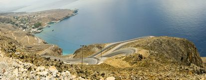 Cretan Shore With Road. Cretan coast in Southern part of the island. White buildings in the background is a town called Chora Sfakion Royalty Free Stock Image