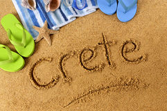 Crete beach writing. The word Crete written on a sandy beach, with beach towel, starfish and flip flops Royalty Free Stock Images