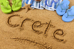 Crete beach writing. Crete beach : the word Crete written on a sandy beach, with beach towel, starfish and flip flops Royalty Free Stock Photos