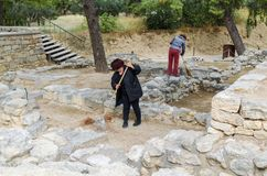 CRETE, GREECE - November, 2017: Workers sweeping the territory o. F the ancient ruines of the Minoan Palace at Knossos. Knossos palace is the largest Stock Photos
