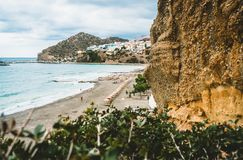 Crete, Greece. View from cliffs to village with marine vessels, boats and lighthouse. View from cliff on Bay with beach. And architecture - vacation destination royalty free stock image