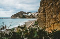 Crete, Greece. View from cliffs to village with marine vessels, boats and lighthouse. View from cliff on Bay with beach. And architecture - vacation destination royalty free stock photo