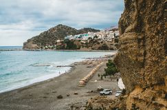 Crete, Greece. View from cliffs to village with marine vessels, boats and lighthouse. View from cliff on Bay with beach. And architecture - vacation destination stock images