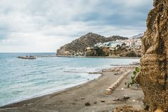 Crete, Greece. View from cliffs to village with marine vessels, boats and lighthouse. View from cliff on Bay with beach. And architecture - vacation destination stock photography