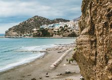 Crete, Greece. View from cliffs to village with marine vessels, boats and lighthouse. View from cliff on Bay with beach. And architecture - vacation destination stock image