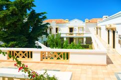 CRETE ISLAND, GREECE, JULY 01, 2011: View on hotel villas for tourists guests. Green tropical palm trees, white houses villas. Cla stock images