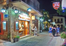 Creten Dinner Time at Malia. MALIA, GREECE - JULY 22, 2014: Creten Dinner Time - People eating dinner outdoors in Greek Tavernas and walking the streets at Malia Stock Image