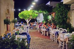 Creten Dinner Time at Malia. MALIA, GREECE - JULY 22, 2014: Creten Dinner Time - People eating dinner outdoors in Greek Tavernas and walking the streets at Malia Stock Photo