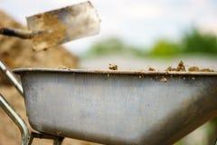 Creusement avec une pelle Lancement du sol dans une brouette images stock
