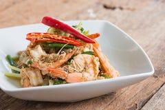 Crevette faite sauter à feu vif avec le curry dans le plat blanc sur le bois brun image stock
